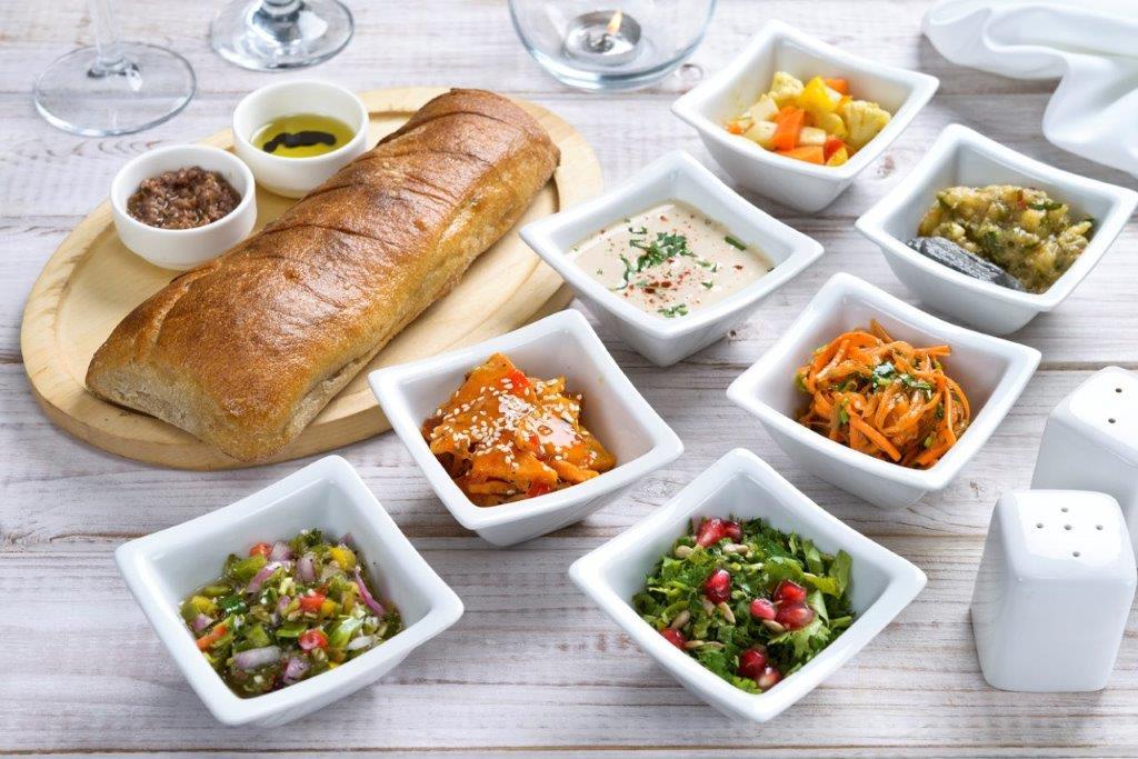 מסעדת לה סרדין אילת לחם מחמצת מקמח מלא עם מטבלים, שמן זית ובלסמי, טפנד זיתי קלמטה ו- 7 סוגי סלטים